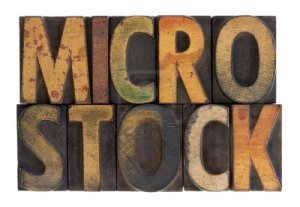 6790061-the-word-microstock-in-vintage-wood-block-type-stained-by-color-ink-isolated-on-white